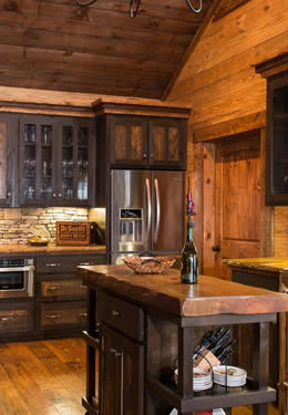 Craftsman custom wood stone kitchen dark brown timber cabinets light brown hardwood floors oversized drawers glass panel inset cabinet doors.