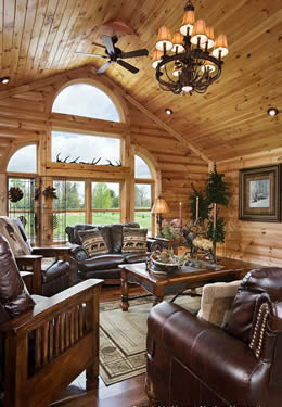 Living room log walls T&G peak ceiling wall of windows dark leather heavy wood furniture dark hardwood floors area rug.