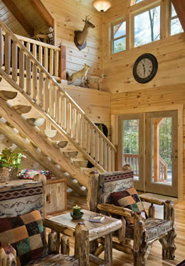 Two story foyer entrance wood doors stairway to loft half log stairs log banister railing hardwood floor custom log chairs.