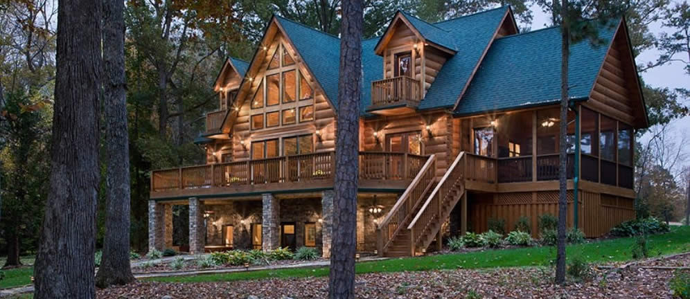 Gold tones three level log home steep gabled black roof large deck screened porch glowing windows at dusk in woods.