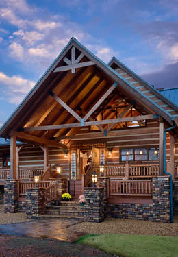 Heavy timber covered A-frame two level front porch entrance stone corners stairway stone underpinning triangle night lighted windows above door.