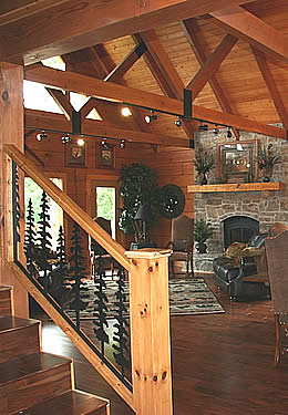 Reddish brown heavy timber great room stone fireplace glass doors dark brownish red hardwood floors wrought iron tree bannister stairway.